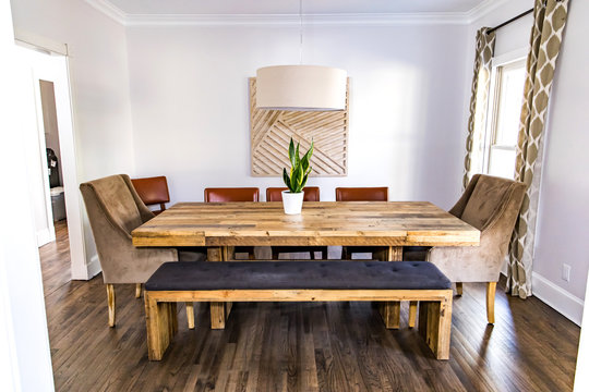 contemporary dining room with upholstered bench and formal chair seating at a large wood table , a window, hardwood floors, and a small plant