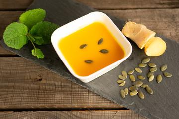 leckere Kürbissuppe im Suppenschälchen mit Ingwer, Kürbiskernen und Minze