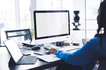 Woman using computer with blank screen