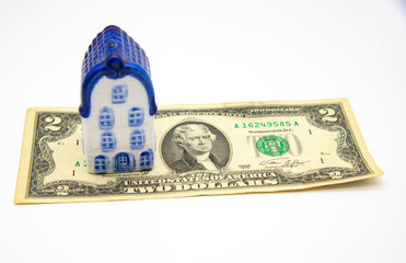 The ceramic house stands on a two-dollar bill. Concept photo as an idea of capital accumulation for improving living conditions.