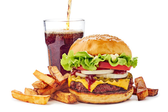 Hamburger, french fries and drink on white