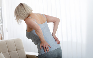 Middle aged woman with pain in the backache and lower back. Concept photo with indicating location...