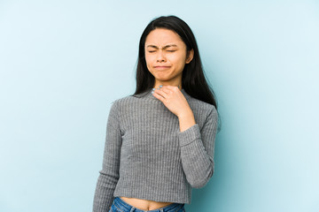 Young chinese woman isolated on a blue background suffers pain in throat due a virus or infection.