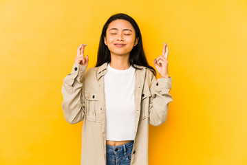 Young chinese woman isolated on a yellow background crossing fingers for having luck