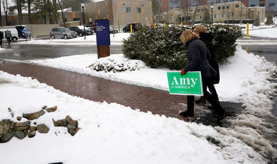 Supporters of Democratic U.S. presidential candidate Senator Amy Klobuchar (D-MN) carry a yard sign in Manchester