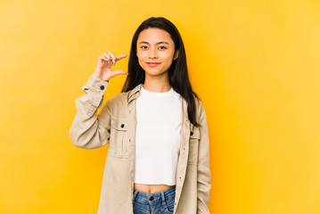 Young chinese woman isolated on a yellow background holding something little with forefingers, smiling and confident.