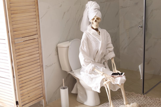 Skeleton in bathrobe with mobile phone sitting on toilet bowl