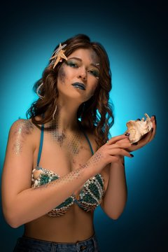 Trendy young mermaid with makeup showing seashell