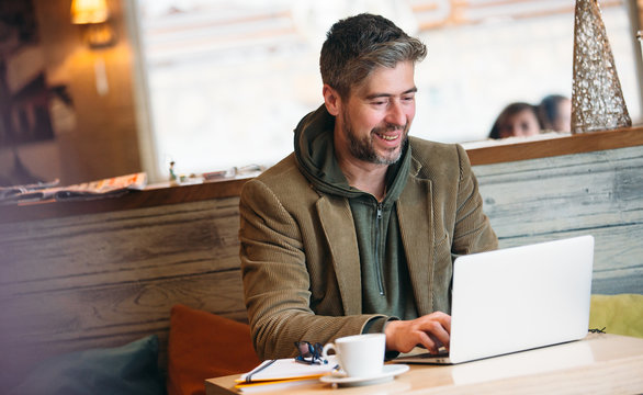 Middle aged handsome man working on a laptop computer, sitting at cafe, lifestyle concept