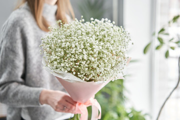 White gypsophila. Beautiful bouquet of mixed flowers in womans hands. the work of the florist at a flower shop. Fresh cut flower.