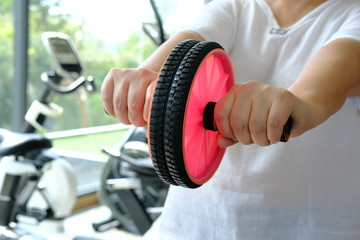 woman in gym with gymnastic wheel roller does exercises for belly