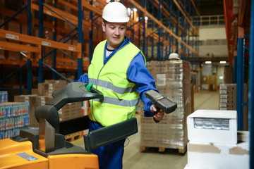 warehouse worker on a forklift scans a box of goods with a barcode scanner