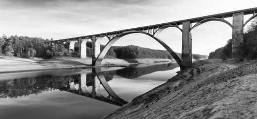 High arched road viaduct above reservoir. Panoramic black and white view. Podolsko Bridge, Czech Republic. Original Vltava river bed of discharged Orlik dam. Muddy bank and mirroring in water surface.