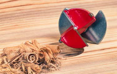 Forstner drill bit detail from below. Red milling cutter on wood background. Sharp steel cutting tool with positioning plate. Boring of precise flat-bottomed hole. Shavings pile. Furniture production.