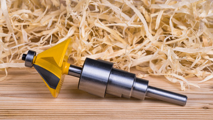 Shank router bit milling cutter detail. Still life with wood and pile of shavings in background. Steel shaping cutting tool. Yellow copying end mill for trimming and shaping in cabinetry. Woodworking.