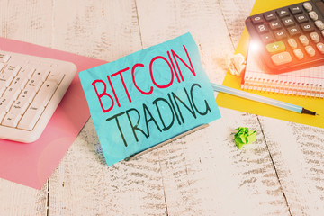 Handwriting text writing Bitcoin Trading. Conceptual photo buying and selling of cryptocurrency in stocks market Notepaper standing on buffer wire between computer keyboard and math sheets