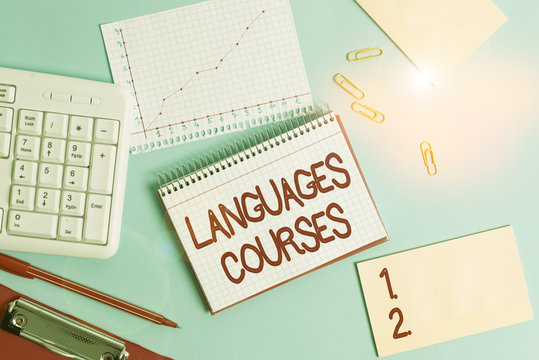 Word writing text Languages Courses. Business photo showcasing set of classes or a plan of study on a foreign language Paper blue desk computer keyboard office study notebook chart numbers memo