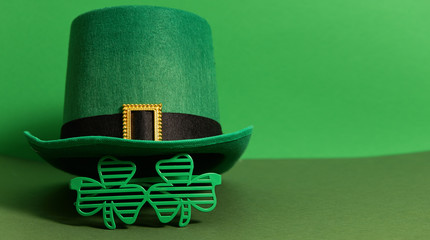 Happy St Patricks Day. Lepricon hat with glasses in the shape of a three leaf clover on a green background. Holiday attributes