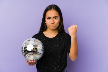 Young asian woman holding a ball party isolated showing fist to camera, aggressive facial expression.
