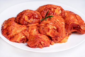 Foto op Canvas Kip Chicken legs in a red marinade on a white plate. Top view. Chicken meat close-up.Dietary meat. Cooking.Raw marinated chicken legs for grill and bbq.Isolate.