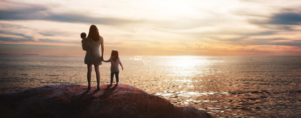 panoramic - mom with her daughters at dusk on the beach looking at the horiz