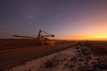 Wide angle picture mining industry equipment reclaimer machine, conveyor belts moving raw copper, silver, gold, from train load out stockyard export to ship load out areas with sunset the background