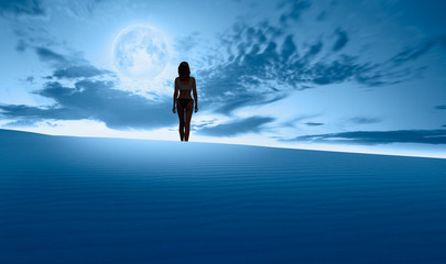 Wall Mural - Silhouette of a beautiful woman standing on the desert - Night sky with blue moon in the clouds on the foreground blue desert (sand dune)