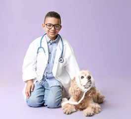 Cute little African-American veterinarian with dog on color background