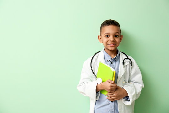 Cute little African-American doctor on color background