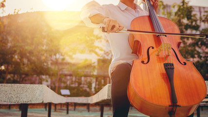 Musician man using a bow to practicing the cello playing with the melodiousness at the sunset....
