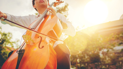 Musician man using a bow to practicing the cello playing with the melodiousness at the sunset. Selected focus.