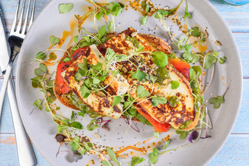 A serving of Baked Ricotta, Capsicum and Pesto placed on a slice of toasted bread, surrounded by salad.