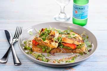 A serving of Baked Ricotta, Capsicum and Pesto placed on a slice of toasted bread, surrounded by salad and a bottle of San Pellegrino sparkling water in the background
