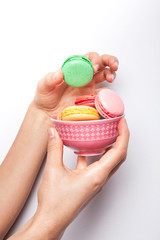 Sweet and colourful macaroons or macaron woman's in hand on white background.