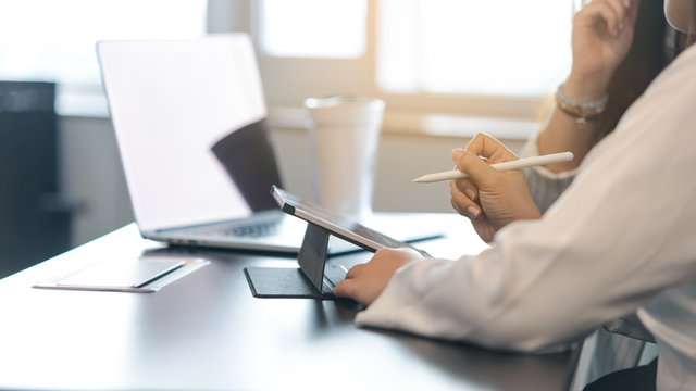 Two young business women sitting at table. First woman holding stylus pen with digital tablet screen. close up side view.