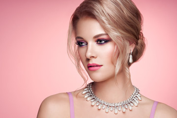 Portrait Beautiful Blonde Woman with Jewelry. Elegant Hairstyle.  Beauty and Fashion Accessories. Perfect Make-Up. Pink Background
