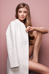 Young elegant woman in trendy white coat. Blond hair, pink background, isolated studio shot. Fashion autumn lookbook. Model girl with long healthy and shiny hair