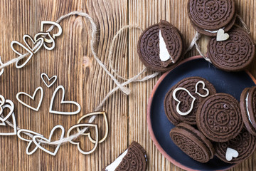 pieces of cookies on a clay plate. hearts made of wood are strung on twine. arranged randomly on a wooden background. happy Valentine's day