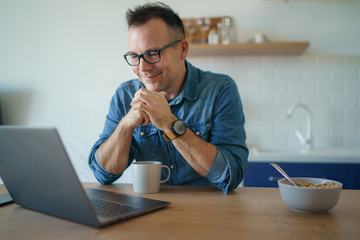 Happy young man, wearing glasses and smiling, as he works on his laptop to get all his business done early in the morning with his breakfast