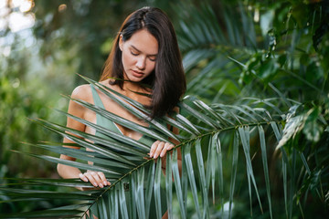 slim young beautiful brunette lady in tropical rainforest , posing and looking down. attractive female with perfect body in green swimsuit stand around green plants, during resort Wall mural