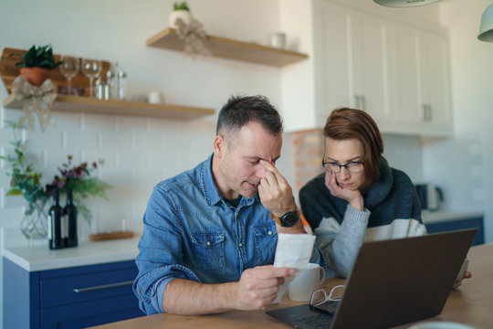 Young stressed Caucasian couple facing financials troubles, sitting at kitchen table with bills, checks and laptop computer and reading document from bank, looking frustrated and unhappy