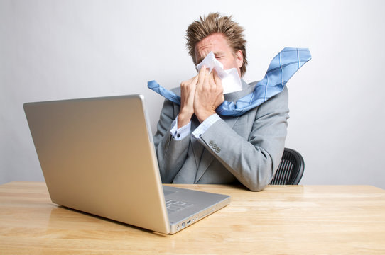 Sick businessman sneezing in front of his laptop computer sitting at his office desk