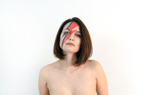 red and blue lightning bolt on her beautiful face. Beautiful girl with original make-up on a white background. Studio photo.