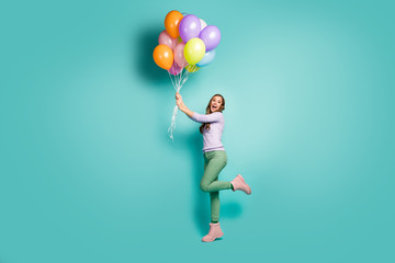 Full length profile photo of pretty funky lady hold many colorful air balloons gonna fly away with wind blowing wear lilac jumper green pants boots isolated teal pastel color background