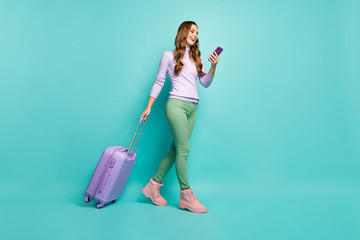 Full length photo of cheerful lady walking airport registration with rolling suitcase browsing telephone wear lilac sweater green pants shoes isolated pastel teal color background