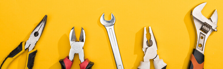 Top view of wrenches and pliers on yellow background, panoramic shot