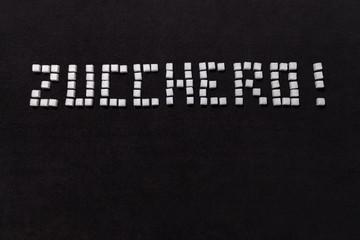 Fototapeta Słowo cukier w ułożone z kostek cukru w języku włoskim na czarnym tle. obraz
