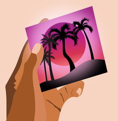 Woman hands holding a picture of beach with palm trees and purple sun in the sky