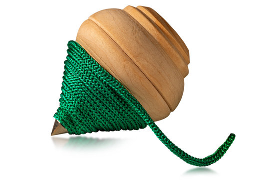 Close-up of a wooden spinning top with a green rope, isolated on white background. Vintage toy