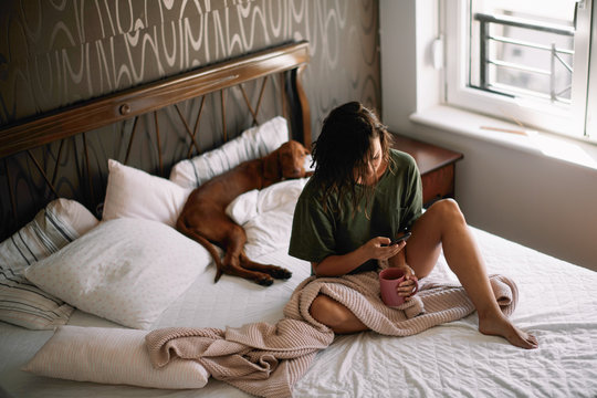 Girl with dog in bed. Woman drinking coffee and using phone.